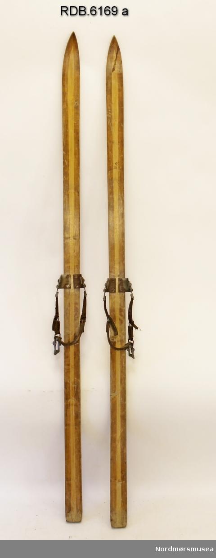 Et par brune helvedski med lys, langsgående midtstripe. Påmontert kandaharbindinger med regulerbare hælreimer av lær med spenner og strammeklemme.