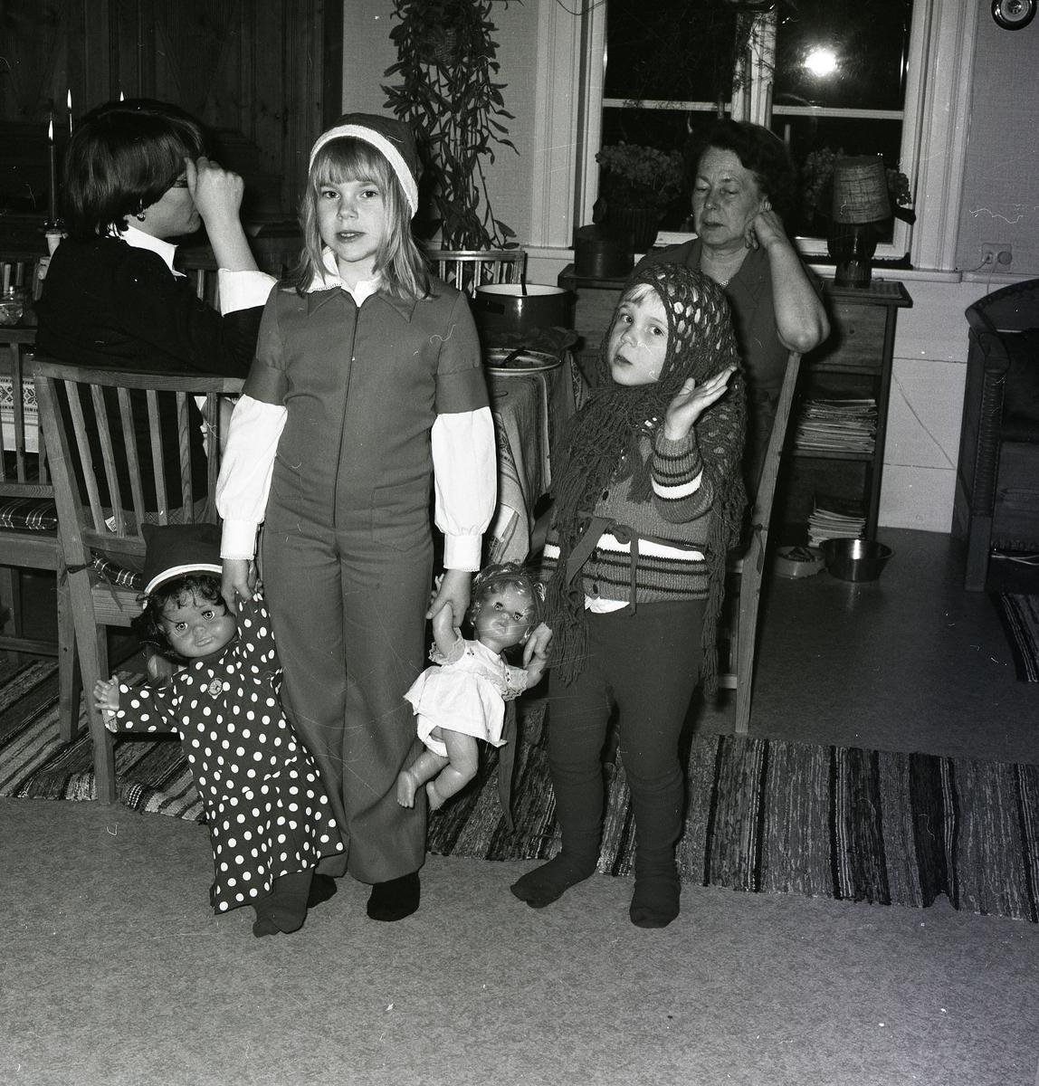 Kvinnor från flera generationers är samlade i ett rum. De äldre sitter vid bordet och samtalar med de yngre leker med två dockor i förgrunden. Flickorna är utklädda med luva och huvudduk när det fotograferas 1978 av Hilding Mickelsson.