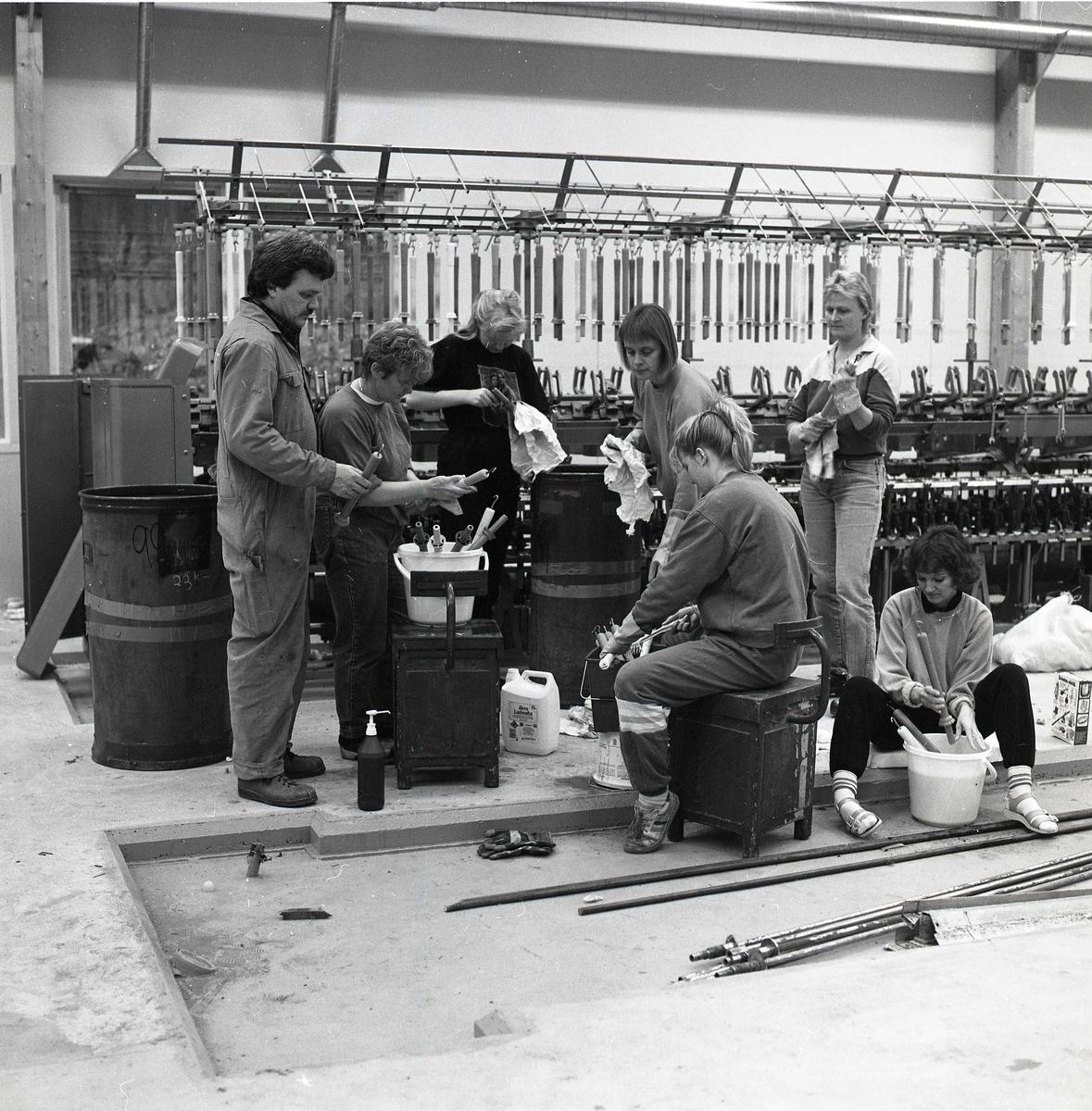 Vid Växbo Linspinneri arbetar sju personer med rengöring av spolar 1989. Inne i en fabriksbyggnad putsar de av spolar från en maskin. På golvet står en såpdunk och pumpflaska intill hinkar med otvättade spolar. Bakom städgruppen syns en maskin för uppträdning och hantering av lin.