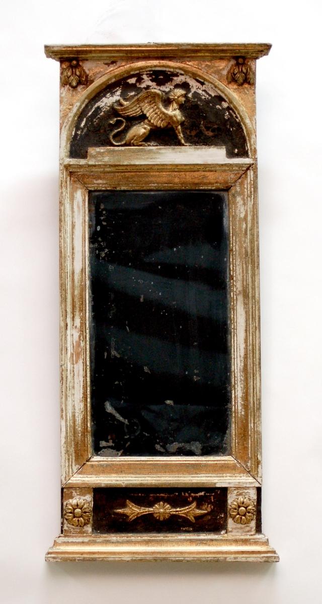 """Kat.kort: Empirespegel, tillverkningstid 1820-1846, rektangulär och guldförgylld. Överstycket har ett svart halvcirkelfält, som innehåller en sfinx i relief. Hörnen upptill har ett bladornament i relief. Understycket men nedsänkt svart rektangulärt fält med ett reliefornament. Två pilastrar i fältet med reliefkorsblomma. Svart stämpel på baksidan """"J W Muhr"""" samt svart hallstämpel på rund påklistrad pappersbit."""