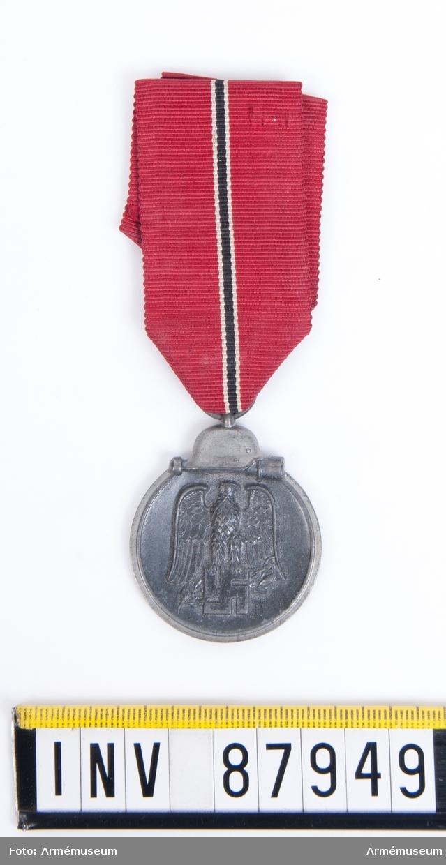 Medalj för deltagande i operation Barbarossa på östfronten 1941-1942. På framsidan en tysk örn med hakkors och på baksidan text samt svärd och lagerkvist.