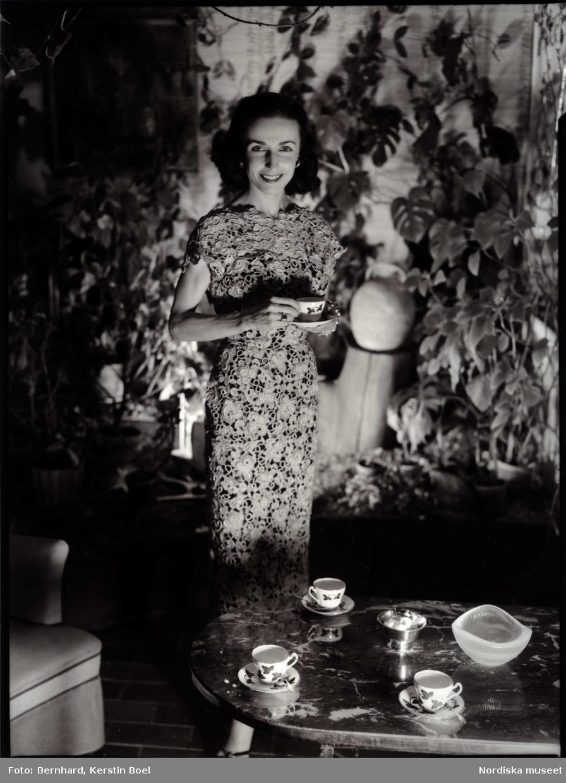 Dansösen Ellen Rasch vid ett bord dukat med kaffekoppar. Värdinnereportage för tidningen Idun.