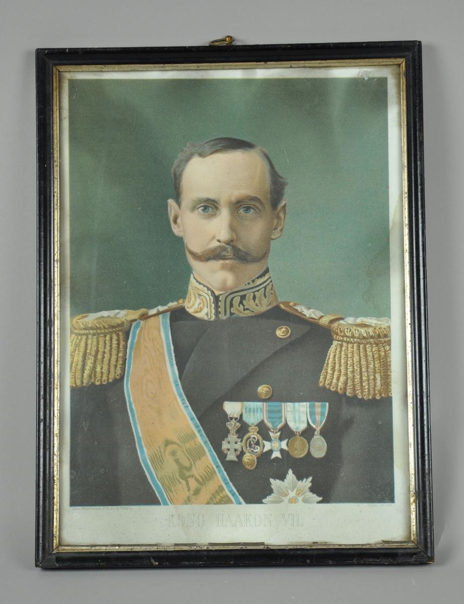 Innrammet portrett av Kong Haakon VII. Svart innramming med kanter av sølv på innsidene.
