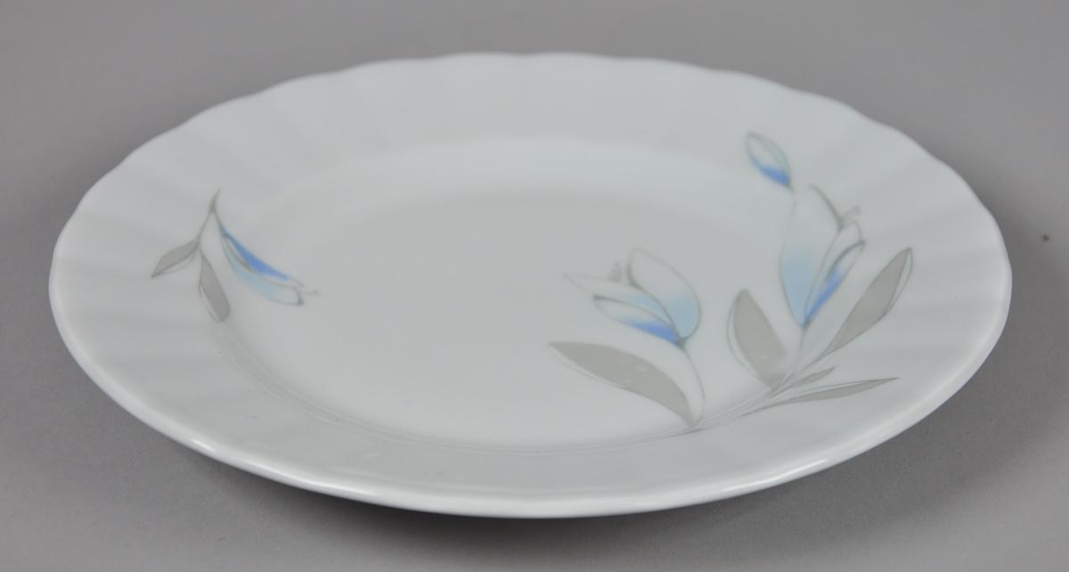 Asjett av glassert keramikk. Skålen har malt dekor på oversiden, med motiv av blader og blomster. Kanten av asjetten har en bølgete form.