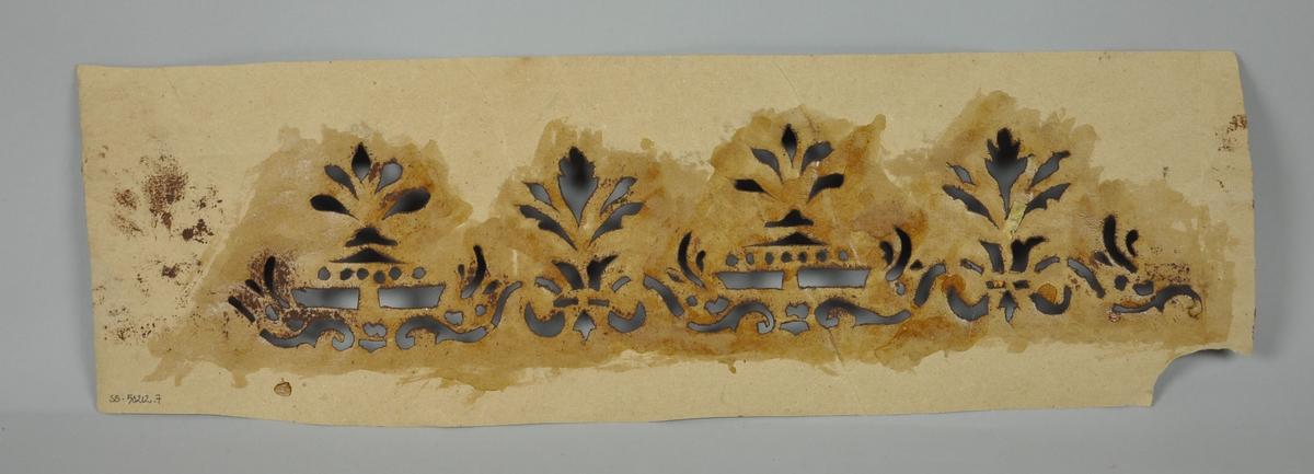 Malersjablong av papir med rester av brun maling.