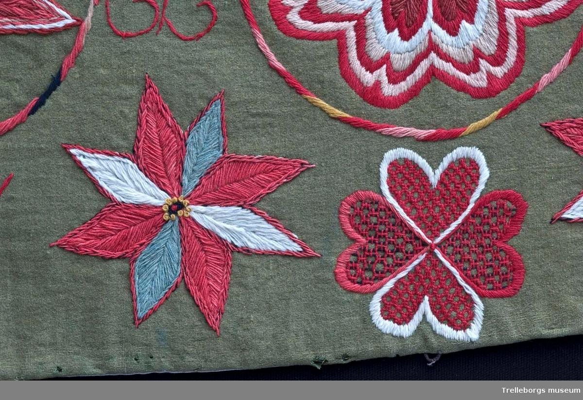 Bottentyg är grön vadmal. Tre stora ringar i kontur utgör huvudmotiv. I ringen i mitten är en stor blomma med 8 kronblad utfyllnad. I de båda ringarna vid sidan är broderat en spetsuddig stjärna med 8 vingpar. Dess centrum är en snedställd kvadrat, sydd i gallerliknande konstsöm. Utmed agedynans långsidor är broderat olika blomsterstjärnor, pionliknande blommor och en blomliknande rundning av 4 st hjärtfigurer. Färger: vitt, gult, svart, blågrått samt många olika nyanser i rött. Baksidan tegelröd yllevävnad.  Enligt katalogen märkt I.W.D.S.  SL. Hjärtrosetter och hjärtan.  Enligt Ernst Fischer, Årsbok från Malmö museum 1971, sid 180: En åkdyna i Tbgs museum har som mittmotiv en runduddig stjärna, omgiven av en ring samt en hjärtrosett över och under, flankerad av spetsuddiga stjärnor. T.h. och v om mittmotivet stora spetsuddiga stjärnor inom ringar. I hörnen varierande blomformer. De ganska svårtydda initialerna skulle kunna tydas som LWD IVH, ehuru bokstäverna då icke är placerade i rätt ordning. IVH skall i så fall beteckna I Vämmenhög.