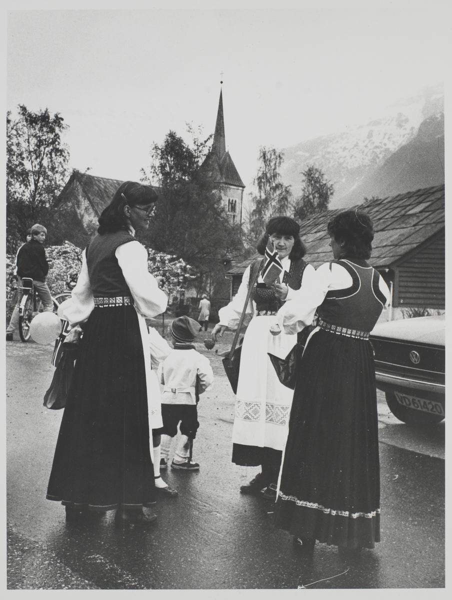 Foto av bunadskledde kvinner og barn på 17.mai på en parkeringsplass foran Ullensvang kirke. Kvinnene bærer Hordalandsbunad.