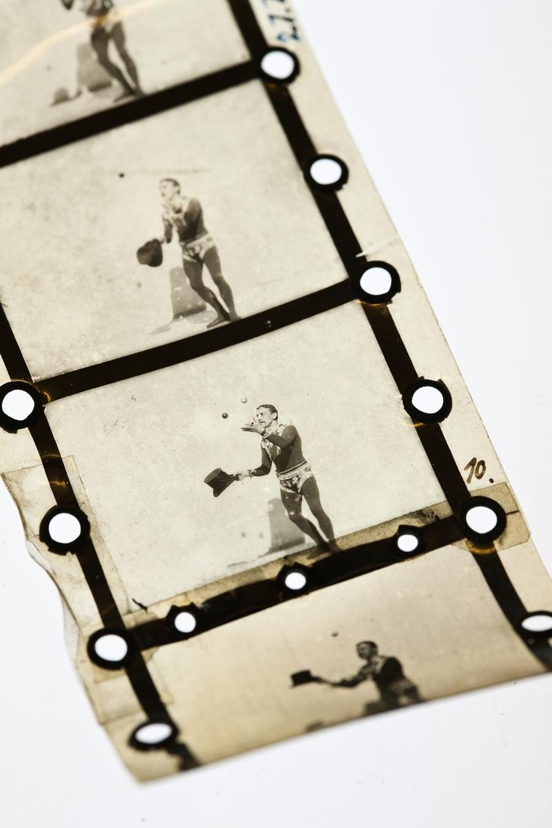 """Bild till utställningen 100 innovationer föreställande innovationen """"filmen"""". Två bitar positiv film av celluloid, 54 mm bred, för visning av """"rörliga fotografier"""" i projektor, """"Bioskop"""" av Max Sklandanowsky (1863-1939). Bildyta:1. 39, h. 265. mm. Den längre filmbiten (12 bilder ur filmen """"Das boxende Känguruh"""" med """"Mister Delaware"""" maj 1895) har hålen numrerade 106-128 med bläckskrift och skarv mellan nr. 112 och 114. Den kortare biten (ur filmen """"Der Jongleur Paul Petras"""" med hög hatt och två bollar, maj 1895) har skarv vid nr. 10. Perforering i båda kanterna med cirkelrunda hål (2 par för var bild), skodda med större öljetter."""