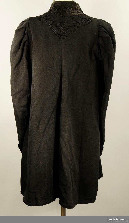 Armene har overslag og store lagte folder på skulderen. Kåpen er foret med svart kypertvevd bomullstoff. Sort lissebroderi direkte på tøyet og på silkesateng sydd på rundt halsen. Sort silkeripsbånd til å knytte saman foran. Kåpen hektes med 4 hekter foran.