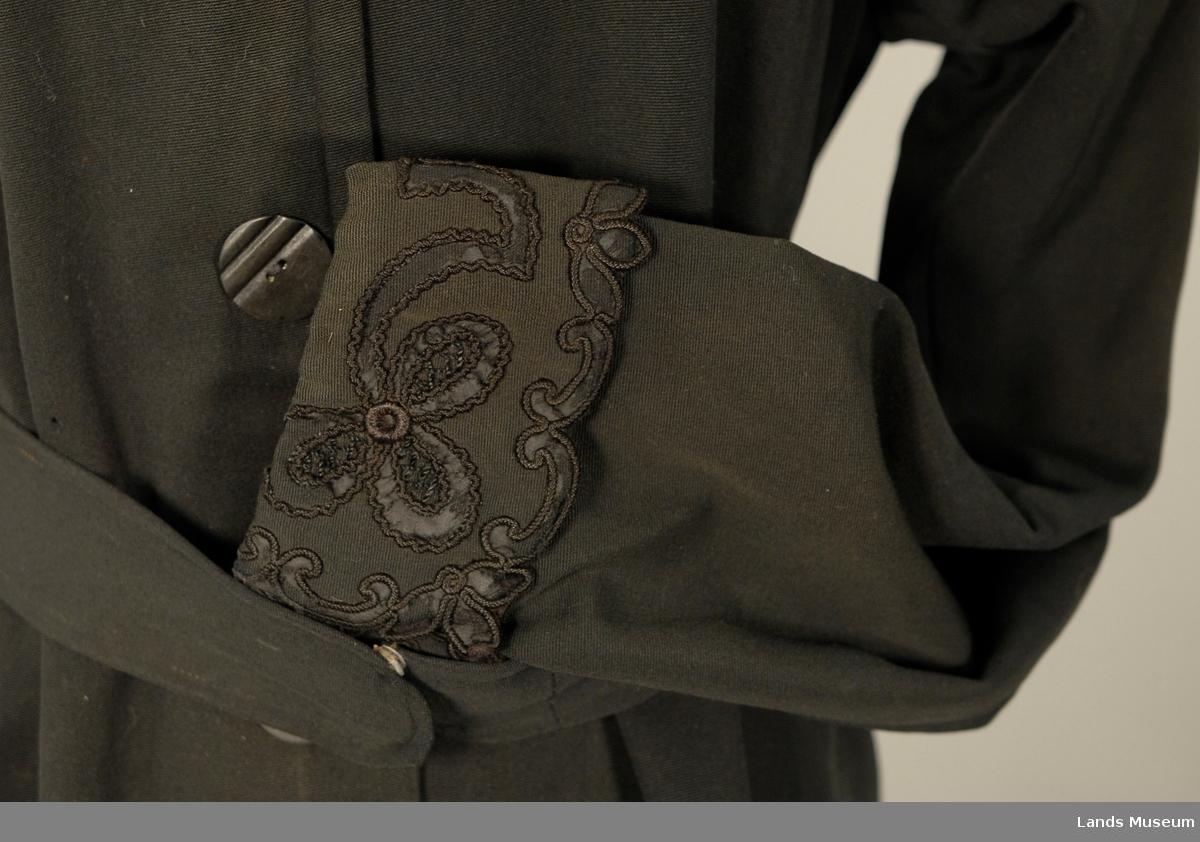 4 knapper foran. Nydeleg broderiarbeide. Kåpa har to folder bak og belte. Sorte lissebroderier (agraman) med underlag av silke på bærestykke foran og bak, på kraven og på oppslag på armene. Stukket rad ca. 0,8 cm innanfor ytterkanten.