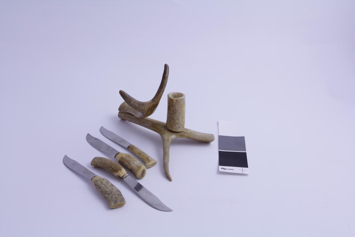 Fire kniver i stål med håndtak i horn. Medfølgende beholder/stativ, også i horn, med påmontert holder i horn eller bein.  Festet med stifter og lim. Horn mest sannsynlig fra rein, siden det står Alta på gjenstanden. Trolig en souvenir.