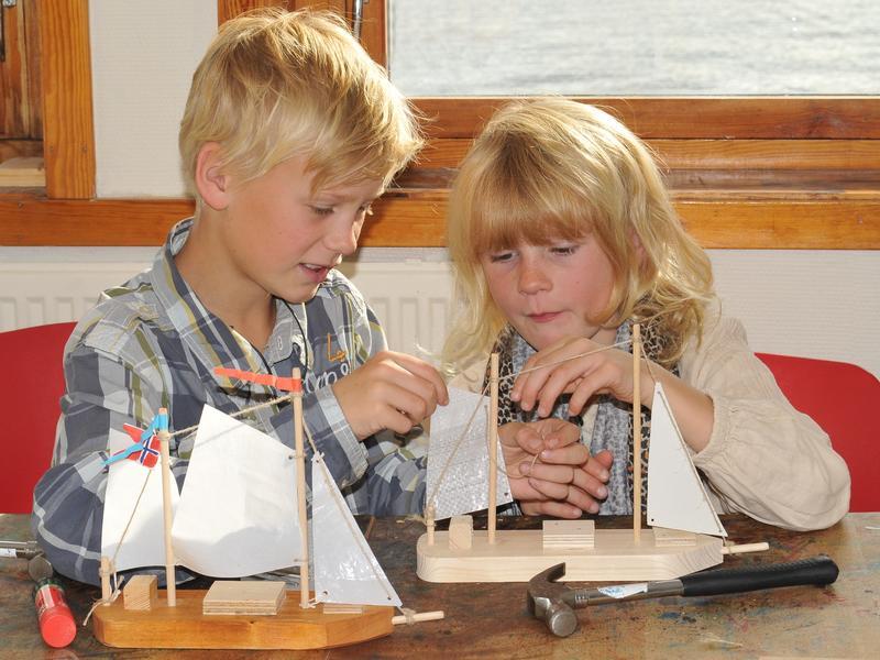 To barn i aksjon i Barnas båtverksted. Foran dem på bordet to lekebåter med seil, samt en hammer. (Foto/Photo)