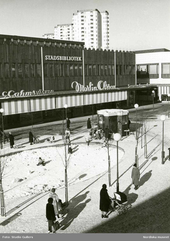 Vy över Farsta centrum med Stadsbiblioteket, G Gahns väskor och Martin Olsson. Flanerande människor och lekande barn.