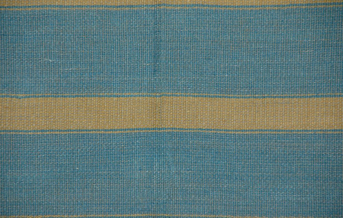 Möbeltyg, 93 x 80 cm. Bomullsvarp, väft i lingarn. Guldgula ränder i oliksidig kypert på blå botten, vävd i tuskaft.  Katalogiserad av Karin Nordenfelt, Elisabet Stavenow, Marie-Louise Wulfcrona-Dagel.