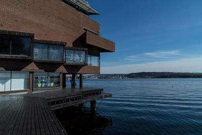 Brygga ved Norsk maritimt museum, blått vann til høyre.