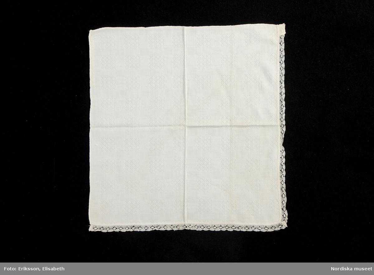 """Huvudliggaren: """"Halskläde, kvadr., vit - bomulls- dräll, m. knyppl. spets å två sidor. fr Leksands sn, Dalarna.""""  Bilaga: Finns ej.  Katalogkort: Finns ej.  Halskläde av vitt bomullstyg vävt i kypertdräll. Fyrkantig duk avsett att vikas till en tresnibb. Smala handfållade kanter runtom. Fastsydd handknypplad uddspets, sockerudd med spindel,  1 cm bred, i kanten  runtom två sidor. /Inga-Lill Eliasson 2007-03-26"""