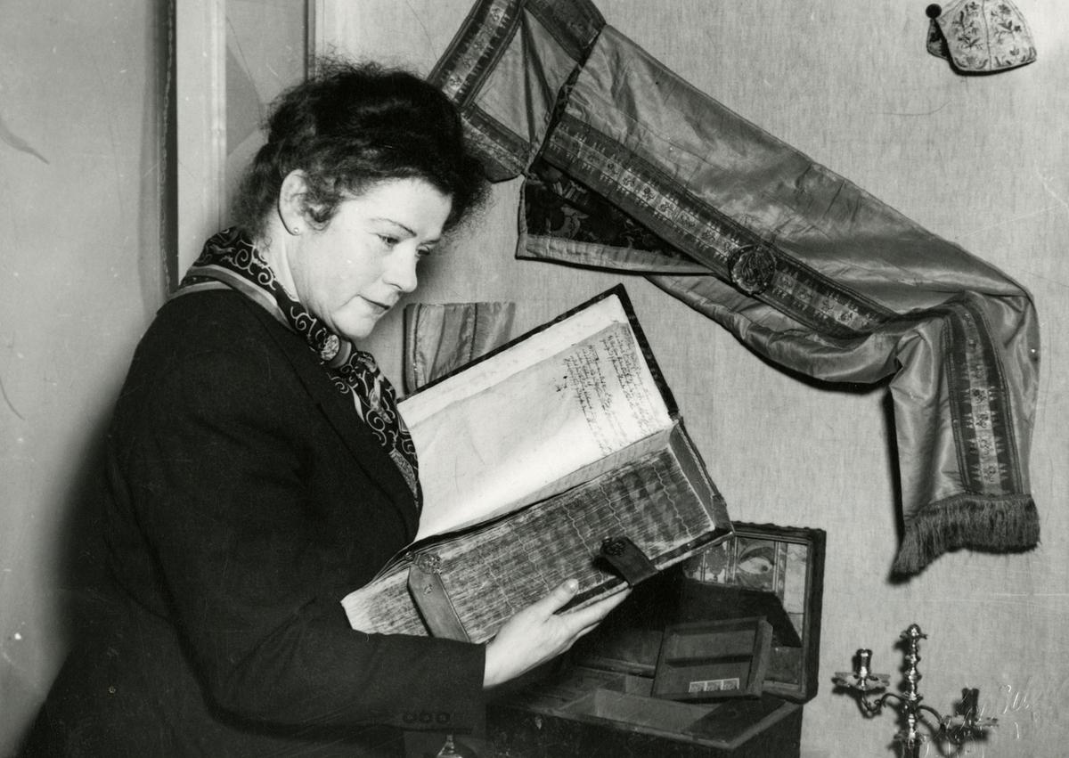 Victoria Bachke med rådmann Jan Wessels familiebibel. Ovenfor bibelen henger Wesselfamiliens dåpsdrakt.