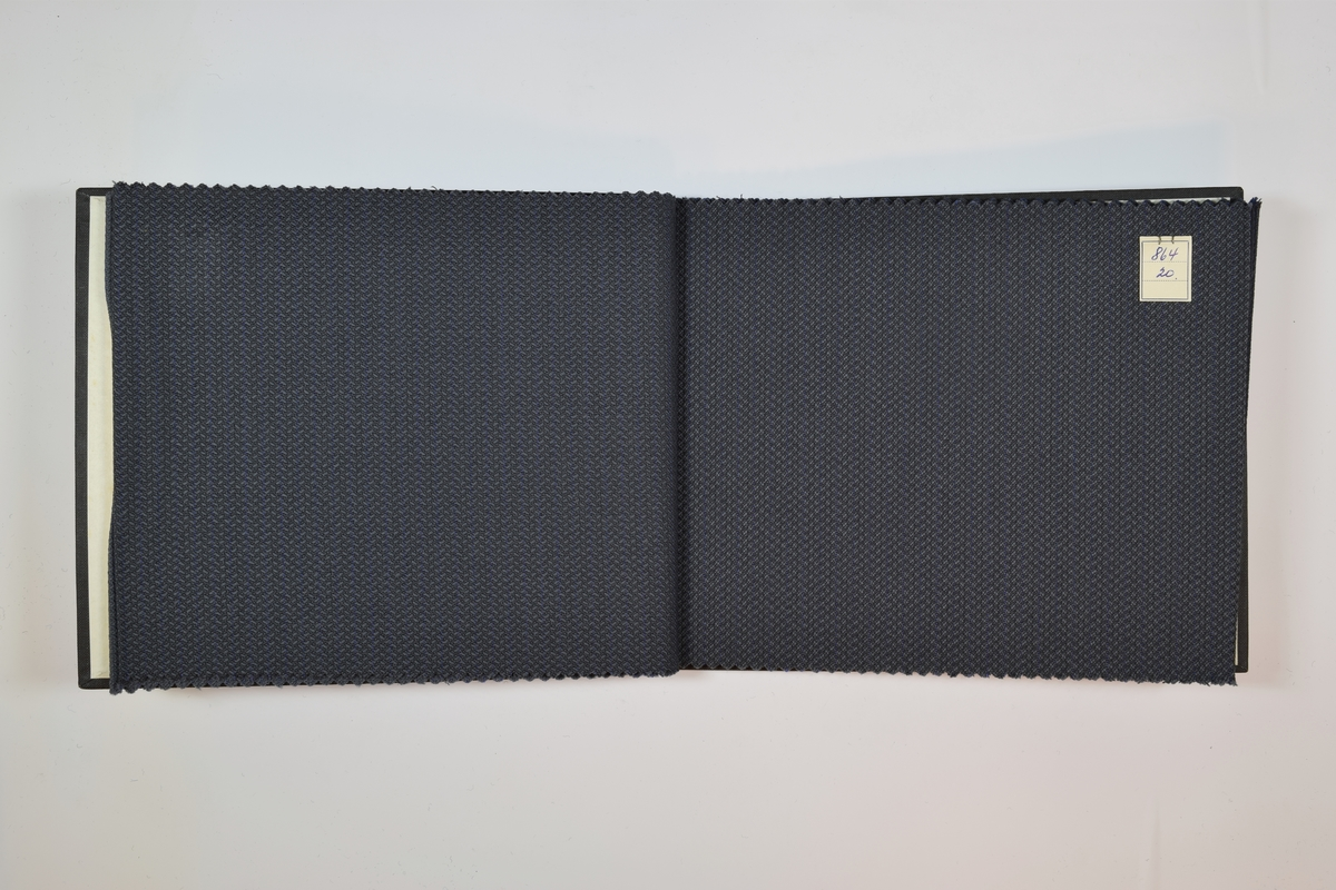 Prøvebok med 6 stoffprøver. Tynne melerte stoff, monokrome i grå eller blå fargetoner. Stoffprøvene ligger brettet dobbelt i boken slik at vranga dekkes. En firkantet papirlapp hvor nummer er påskrevet med penn er festet til stoffet med metallstifter.   Stoff nr.: 864/18, 864/19, 864/20, 864/21, 864/22, 864/23.