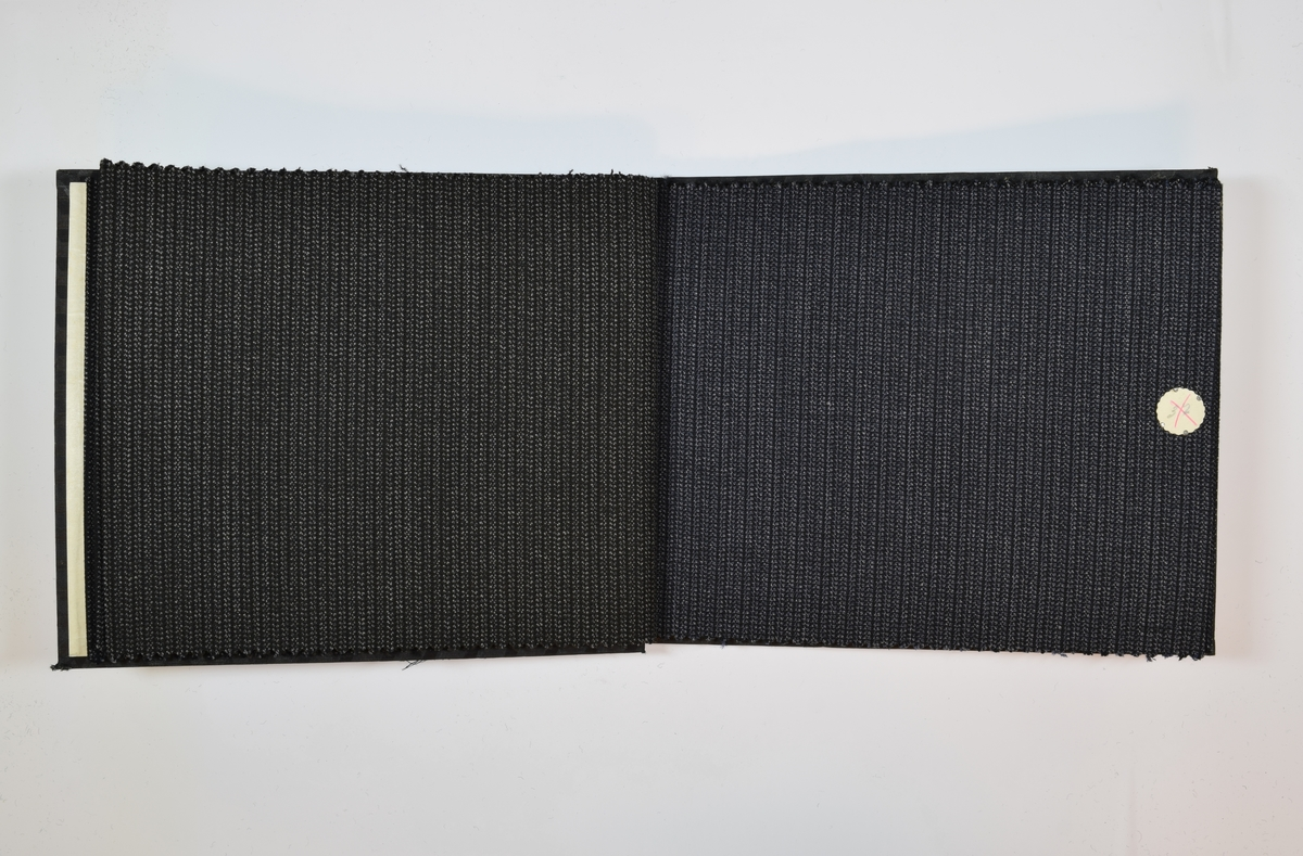 Rektangulær prøvebok med 6 stoffprøver. Relativt tynne melerte stoff med striper eller fiskebensmønster. De tre første stoffene i boken har samme vevmønster, bare ulike fargenyanser, de tre siste har ulike vevmønstre, men alle en blå fargetone. Stoffene ligger brettet dobbelt i boken slik at vranga dekkes.  Stoffene er merket med en rund papirlapp, festet til stoffet med metallstifter, hvor nummer er påført for hånd. Alle numrene er krysset over med en rød fargeblyant. Påskriften på innsiden av forsideomslaget indikerer at alle stoffene i boken har kvalitetsnummer 1566.   Stoff nr.: 1566/34, 1566/35, 1566/36, 1566/37, 1566/39, 1566/40.