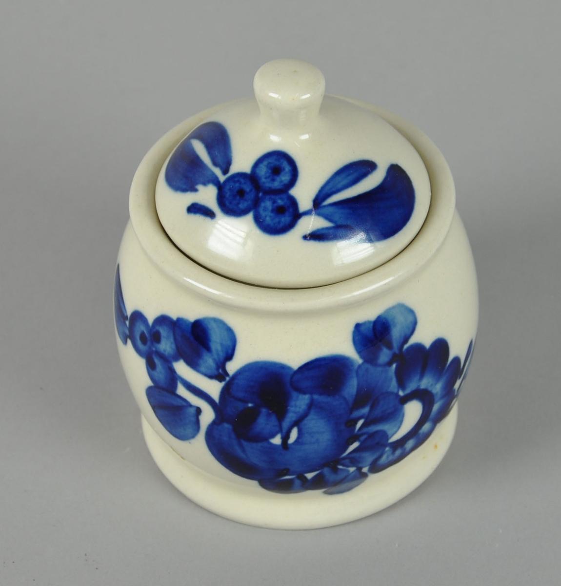 Sukkerskål  med lokk, av glassert keramikk. Har påmalte striper og blomster i blå farge. Lokket har knott på toppen.