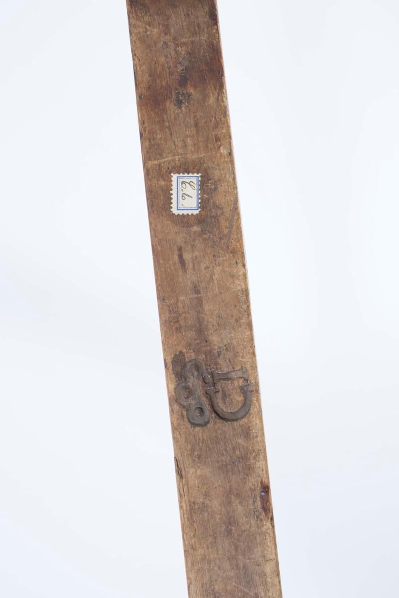 """NTM: """"Fra snekkerverkst. loft i Kongsberg. Er gjordt ved Sølvverket."""" Satt sammen av en tredel og en metalldel. På begge sider av tredelen er det skåret inn ei krone med bokstavene CI under (Carl Johan)."""