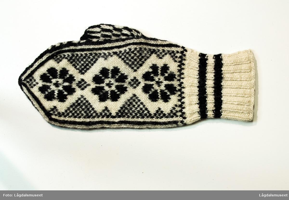 Strikket votter i svart og hvit med tre åttebladsblomster som motiv.