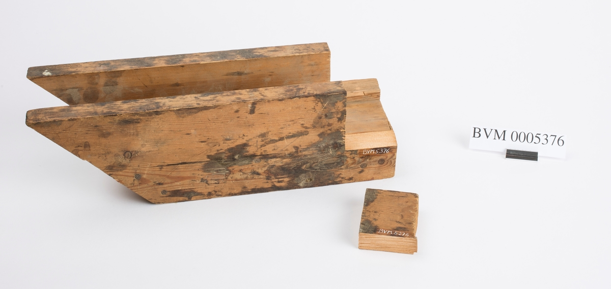 Vinkelen i enden er 45 grader. Ser ut til å ha vært brukt som sagkasse for å sage slike vinkler. To biter i enden er knekt av. Den er løst lagt ved.