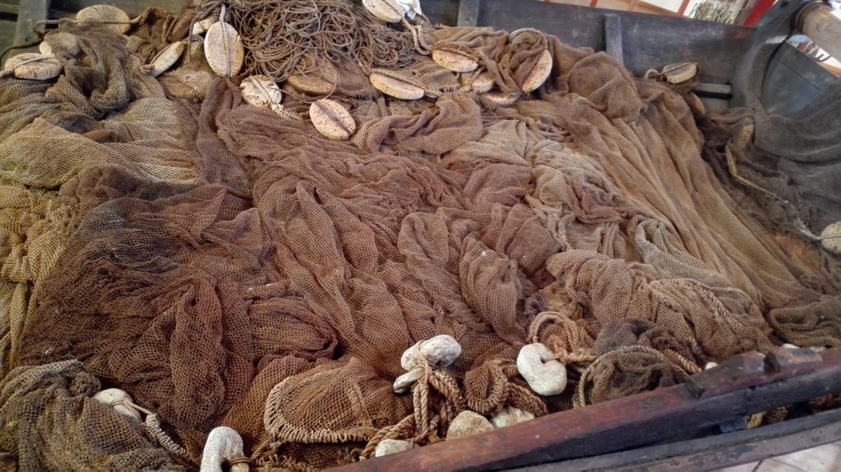 Brislingnot av bomull, med naturkork som flyteelement og gjennomhola stein som søkke.  Maskestørrelse 0,9 ca, frå knute til knute-