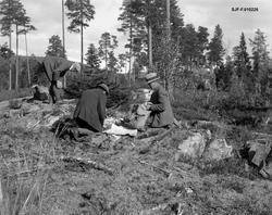 Kvilestund under jakttur i skogen, antakelig i Telemark, høs