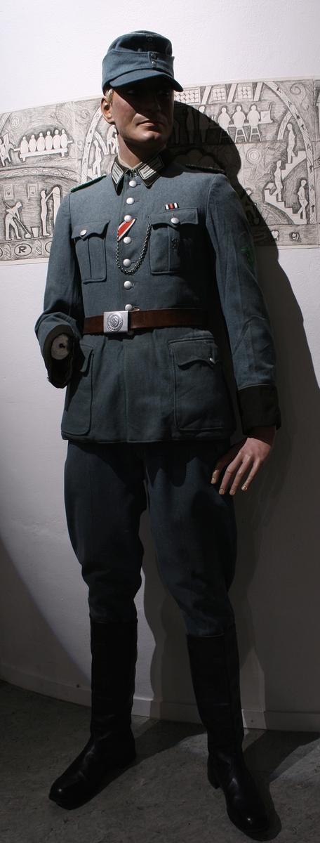 Full uniform med støvler. På brystet har den en pins (Politiets dag 1942), en bånd (Minne-/deltakermedalje 1914-1918) og EK. 2. klasse bånd. Den har også fløyte i brystlommen.   Skulderdistinksjoner til en oberwachtmeister  I lommen var det stoff lapper og sytråd med nål.   På beltet har den pistolhylster med Walther PP magasin.