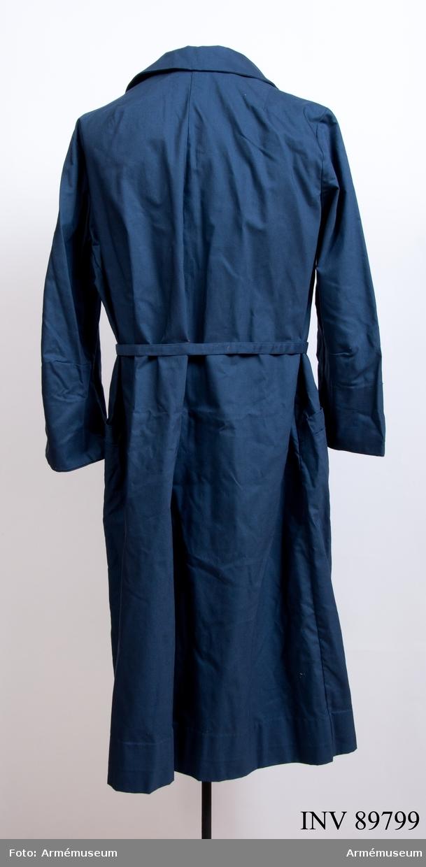 """Rockklänning av blått tyg med Svenska Röda korsets märke på överärmen. Etikett i nacken med text: """"Erling Richard 44"""". Med samhörande skärp och tre nålar med röda korsetsymbol."""