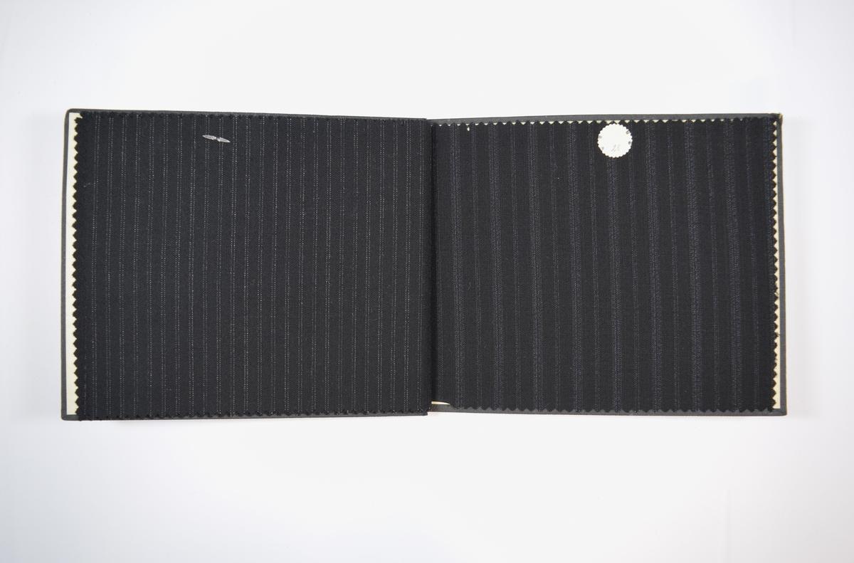 Rektangulær prøvebok med fire stoffprøver og harde permer. Permene er laget av hard kartong og er trukket med sort tynn tekstil. Boken inneholder relativt tynne, tette, sorte stoff med ulike stripemønster. Baksiden/vranga er mye jevnere uten stripemønster i veven som finnes på retta. Stoffene er merket med en rund papirlapp, festet med metallstifter, hvor nummer er påført for hånd.   Stoff nr.: 2120/25, 2120/26, 2120/27, 2120/28.