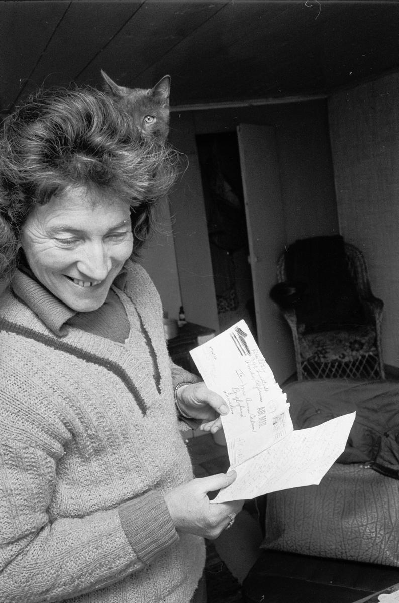 Clary Huldt med katt på axeln läser brev, Riala, april 1967