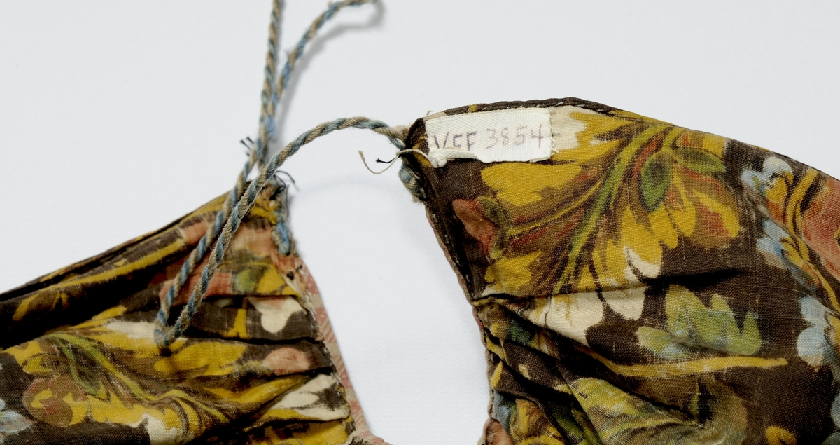 Forkle i brunt bomullstøy, med trykt blomstermotiv i forskjellige farger. Forkledet har handsydd skøyt på høgre side. Glatt stykke (4,5 cm) midt framme øverst med 13 små folder på kvar side. Kanta med eit anna bomullstøy øverst, tvinna snor til band i kvar side. Falda i eine sida og nedrekanten med smal fald. Den andre sida er jarekant.