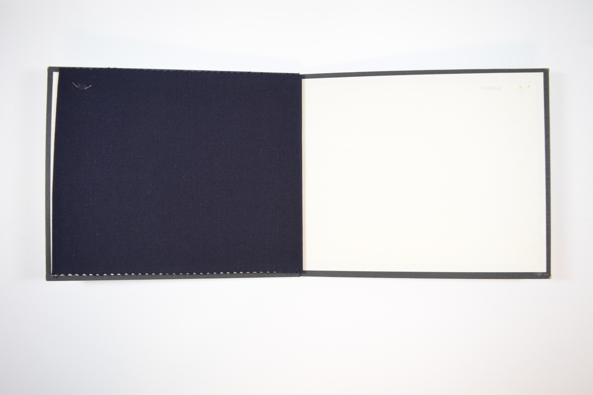 Rektangulær prøvebok med harde permer og én stoffprøve. Permene er laget av hard kartong og er trukket med sort tynn tekstil. Boken inneholder ett relativt tynnt og tett, ensfarget, sort stoff. Kyperbinding/diagonalvev. Stoffet ligger brettet dobbelt i boken slik at vranga skjules, men mønsteret er det samme på baksiden. Stoffet er merket med en firkantet papirlapp, festet til stoffet med metallstifter, hvor nummer er påført for hånd.   Stoff nr.: 4600/sort.