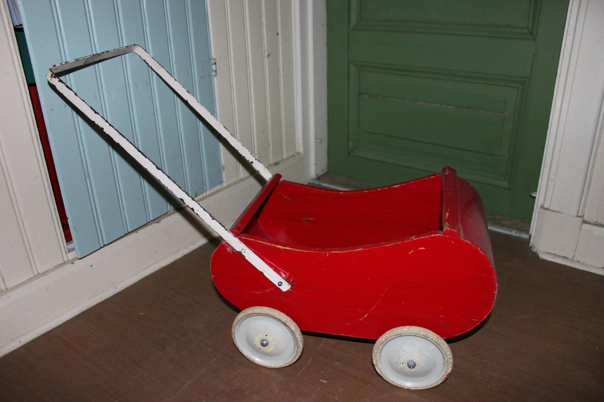 Röd dockvagn i trä med svängt bakparti och framparti. Metallhandtag målat i vitt Hjul i metall från början vitmålade. Ytterdel av hjul i vit gummi.