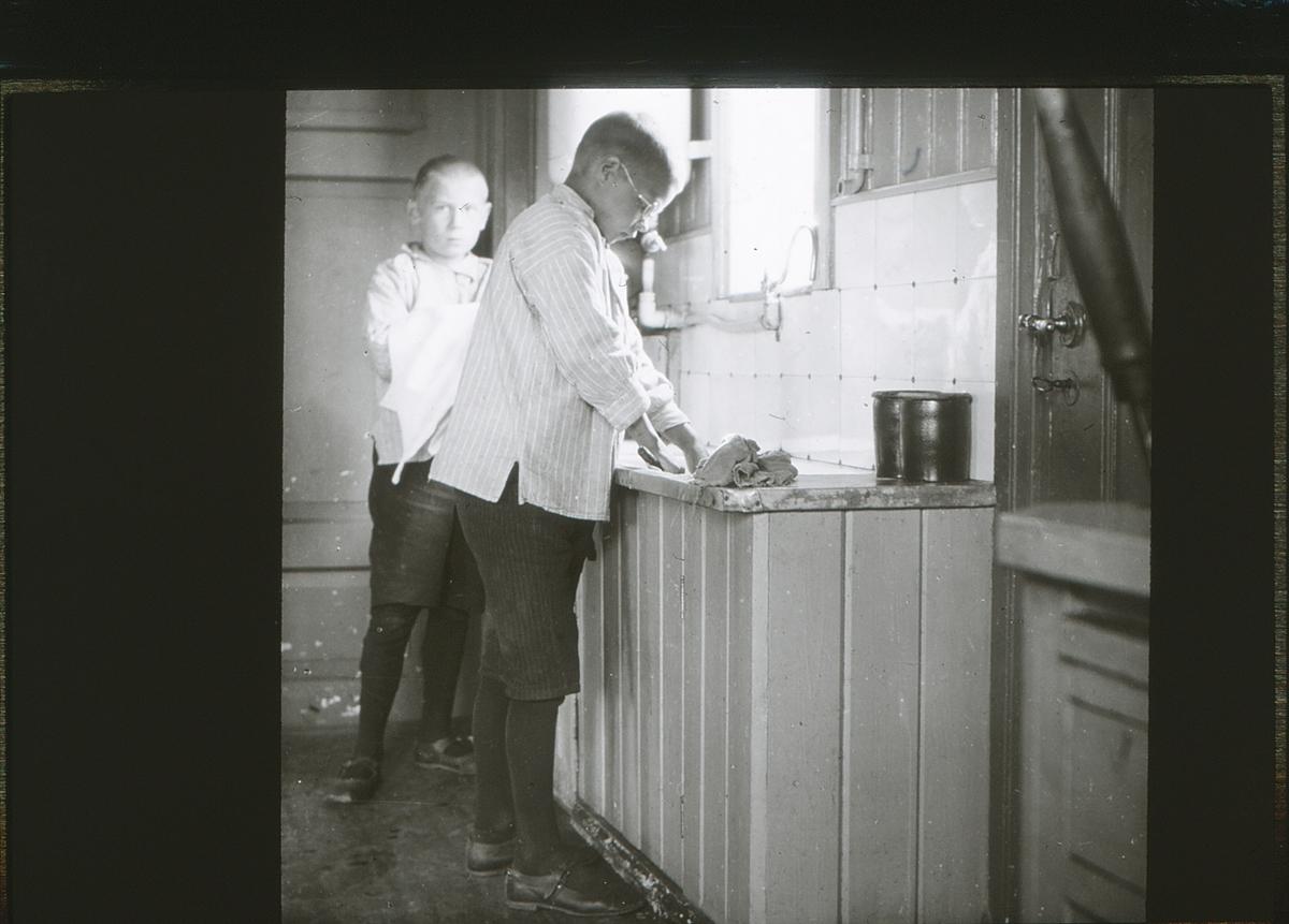 To friluftsskolegutter vasker opp.