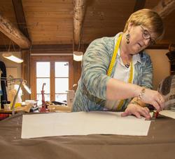 Syerske har lagt mønsterpapir på tøystykke og merker opp søm-monn med kritthjul. (Foto/Photo)