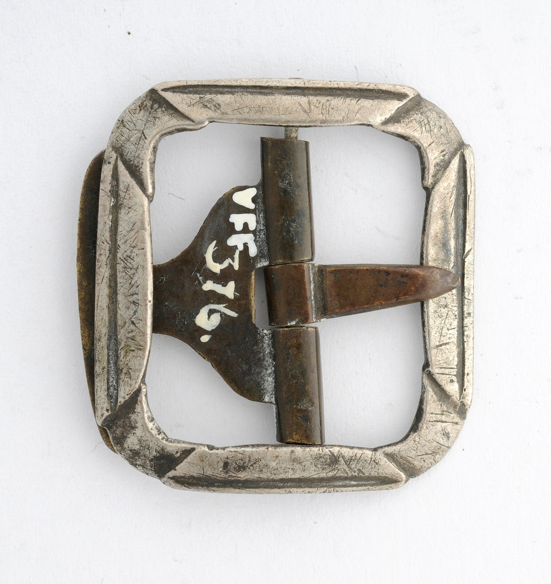 """Knebandspenne støypt i sølv.  Rektangulær form. Lite bøygd. Stolpe, kalv og tann smidd i messing ?. Kalven har ein """"mothake"""". På baksida fleire stemplar. (sjå foto)"""
