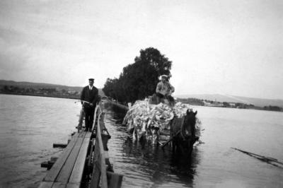 Svart-hvitt foto fra 1927. Gangbru med mann og hestetransport med stort lass som kjører på ordinær bru i flomvann.