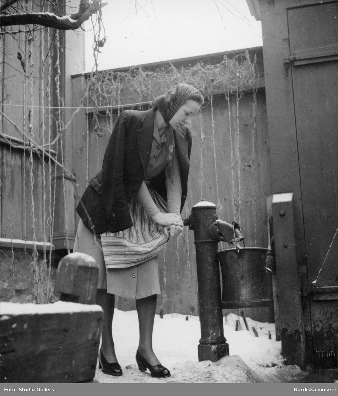 Fru Birgitta Törnqvist pumpar vatten på en bakgård på Mäster Mikaels gata 9, Södermalm, Stockholm.