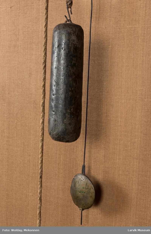 Urskive i blikk med sorte romertall festet på forsiret jernskive. Messingplate innenfor urskiven. Et stort og et lite lodd henger i rep, opprinnelig 2 store og 2 små lodd. Pendel i messing, konsoll av tre.