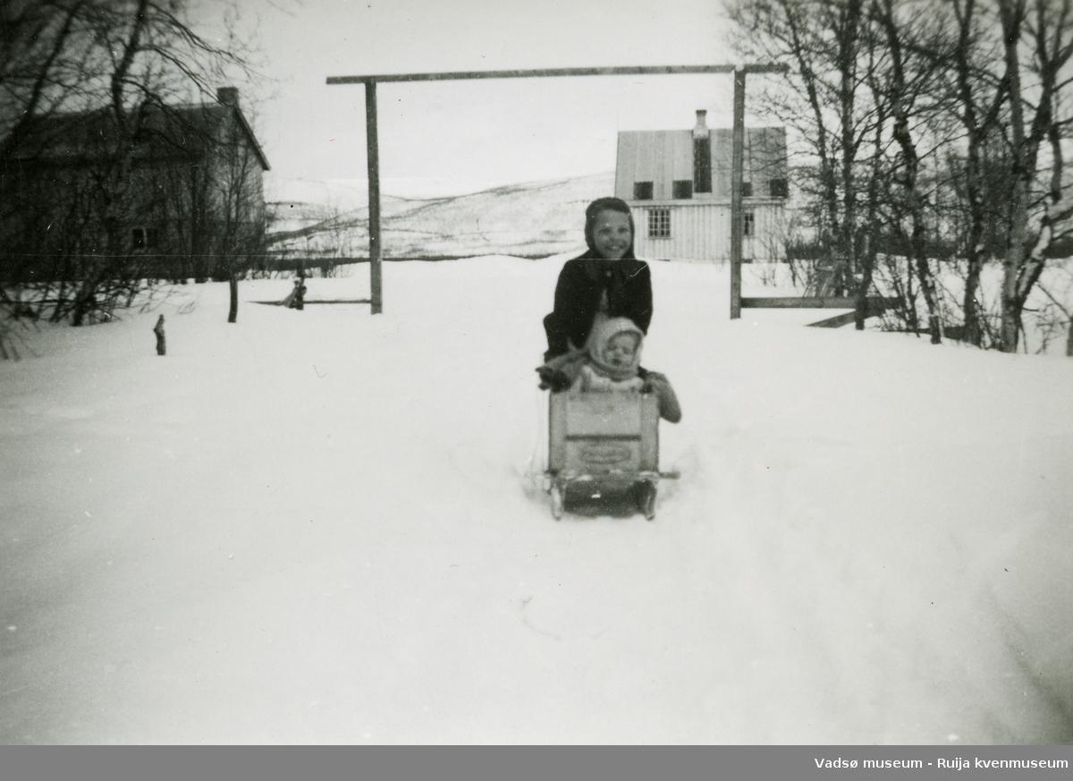 To barn på sparkstøtting, sett mot nord. Antatt å være i Vadsø-området, etter krigen.