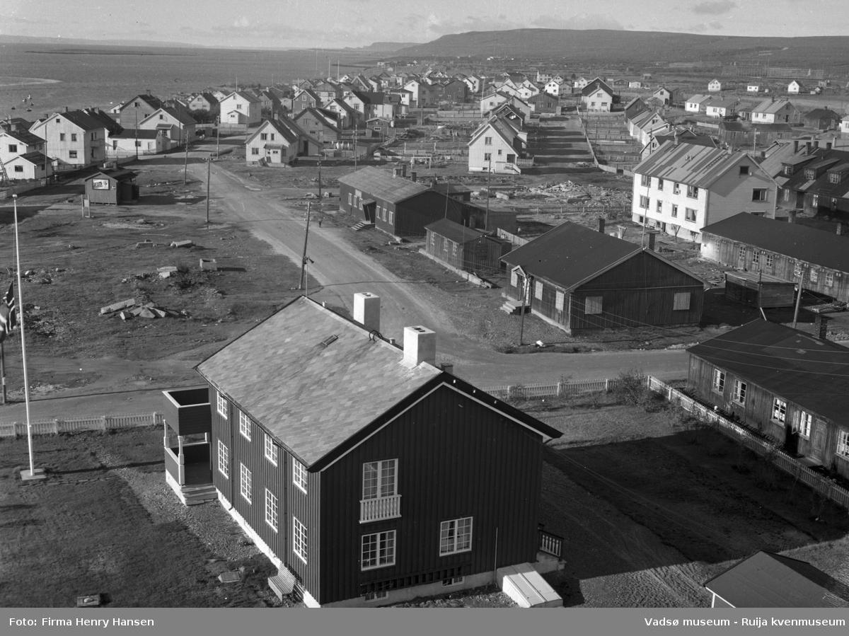 Vadsø 1957. Bildet er tatt fra kirken, om sto ferdig i 1958, mot vest. Vi ser prestegården i forkant av bildet med flagget på halv stang. Langs veien midt i bildet en del brakker fra gjenreisningstiden. Denne veien er sannsynligvis senere regulert bort. Til venstre i bildet bolighus langs Damsveien og fjorden med fiskebåter og Vadsøya i bakgrunnen. Til høyre og lengst fra kamera ses fiskehjeller rett bak bebyggelsen.