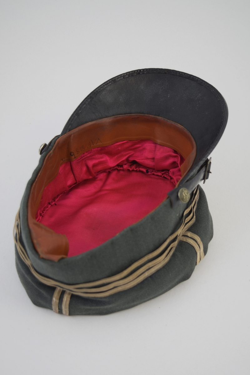 Form: a) Uniformslue: oval pull, rette kanter, påsydde sølvbånd.