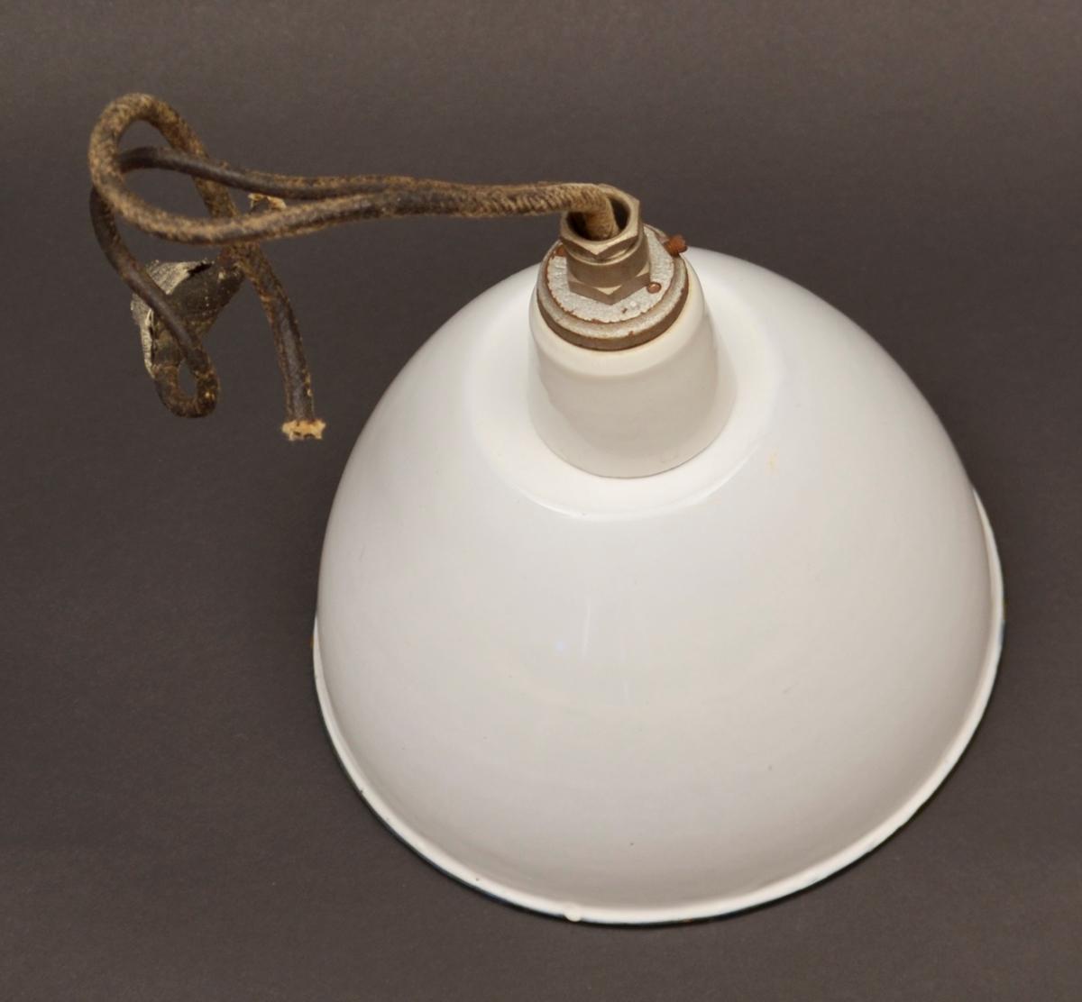 Elektrisk hengjelampe. Skjerm i emaljert jarn, kvite med svart kant nedst. Lampehaldar og pærehaldar i kvitt porselen. Metall øvst. Leidningsstump stikk ut øvst. Leidningen er dobbel med ein slags vaksa, tekstil yte.