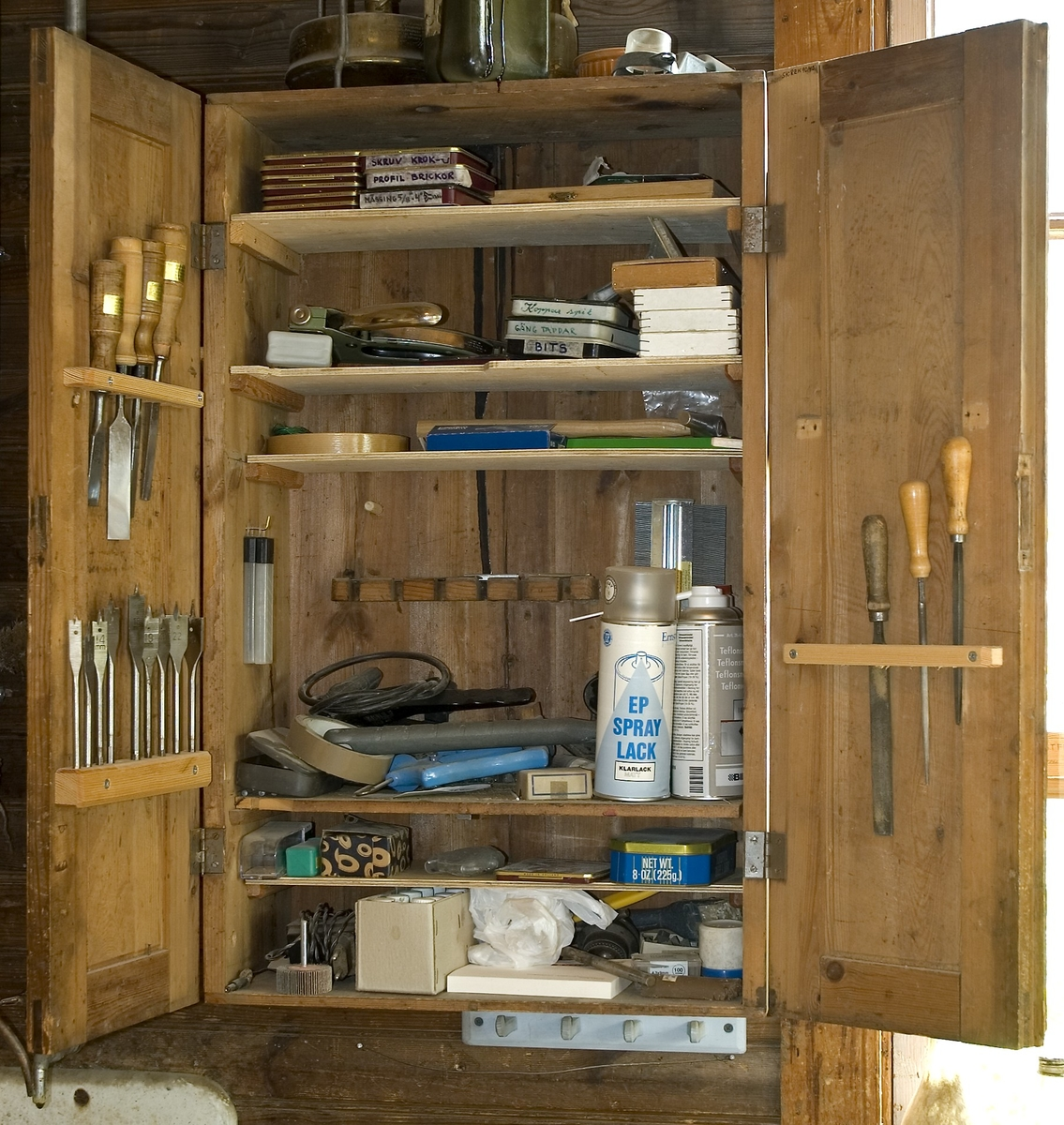 Skåp av trä för förvaring av verktyg. Verktygsskåpet har två dörrar som är tillverkad med ram och fyllning. Skåpet är omålat. På skåpet är 10 inristat på den ena dörren.  Funktion: Möbel för förvaring av verktyg