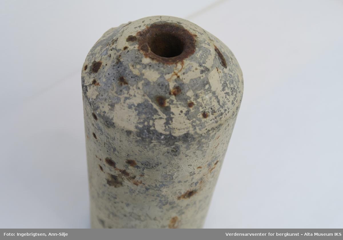 Sylinderformet sementrør med innstøpte jernsplinter. Toppen av røret har en svak pyramideformet avslutning. Hullet som går i gjennom røret er smalt i toppen og utvider seg nedover til bunnen hvor åpningen er størst.