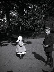 Två barn på Tuna gård. Flickan leker med pinne och rep.
