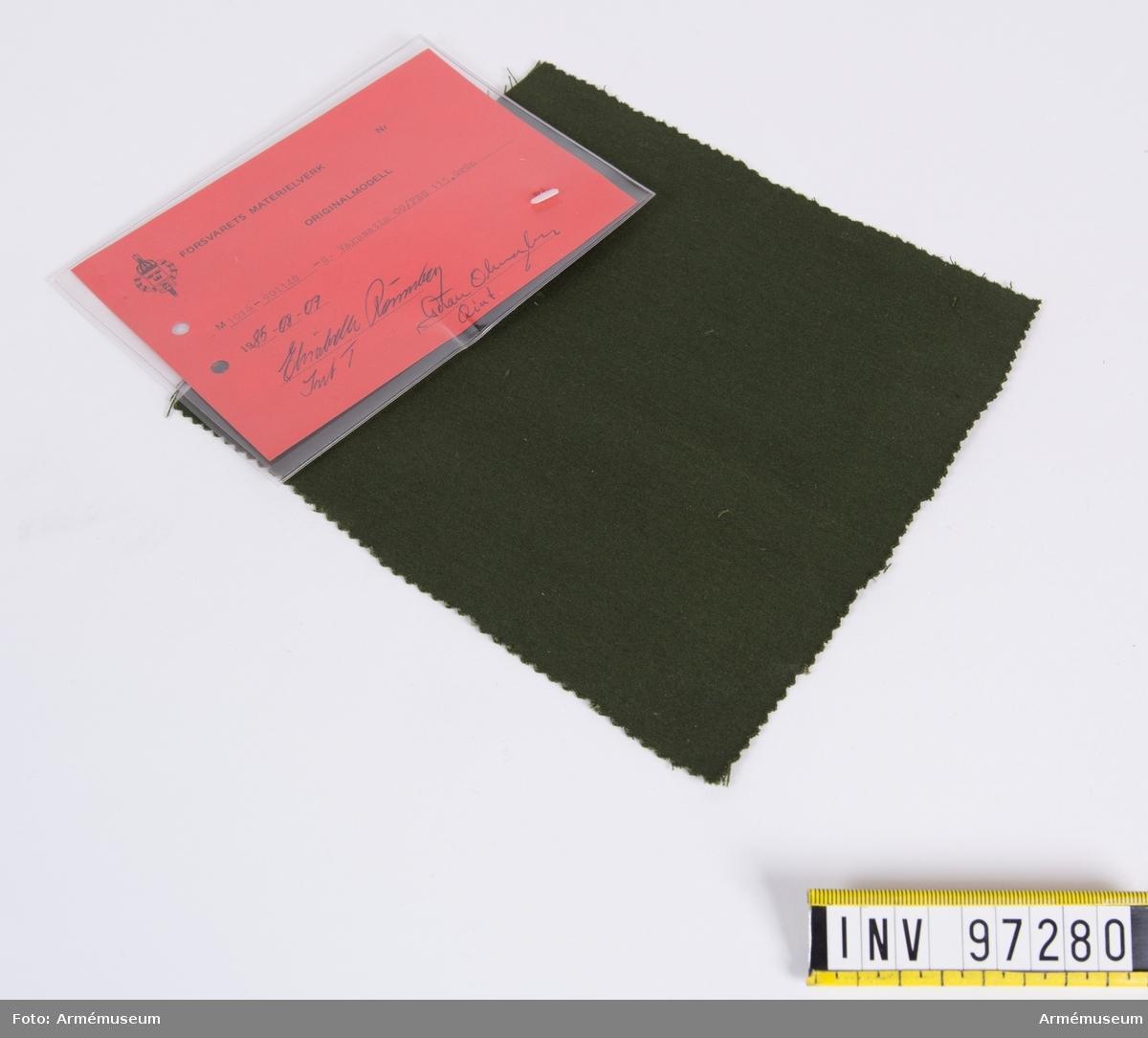 """Vidhängande modellapp med text: """"Försvarets materielverk. Originalmodell. M 1016-901548-8. Varpsatin CO/PES 115, grön. 1985-08-07. Elisabeth Rönnberg IntT, Göran Olmarker QInt."""""""